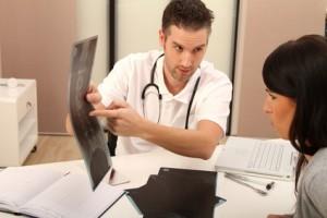 Arzt plus Frau schauen sich Röntgenbild an